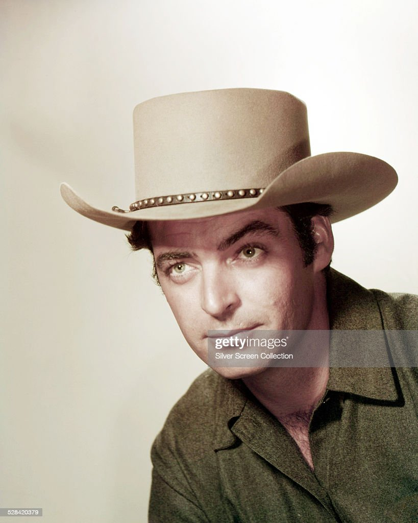 American actor Rory Calhoun wearing a cowboy hat in a promotional portrait for 'Powder River' directed by Louis King 1953