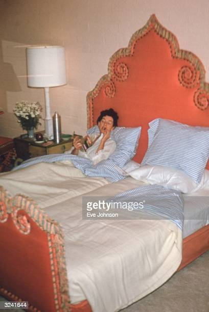 American actor Rosalind Russell eats in bed in her suite at Elizabeth Arden's Maine Chance Resort Scottsdale Arizona