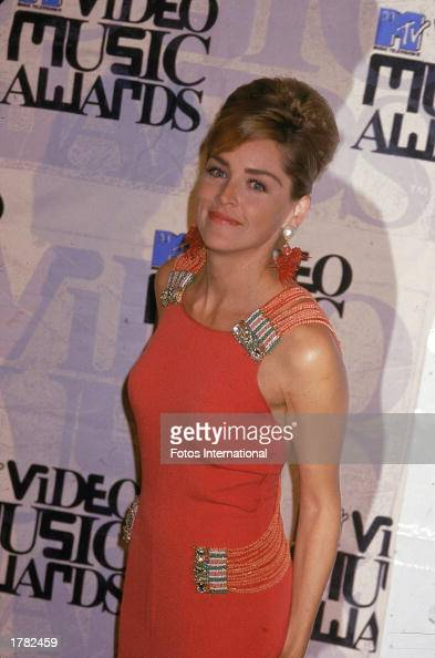 American actor Sharon Stone posing in an orange dress and her hair in a bouffant at the MTV Music Video Awards 1993