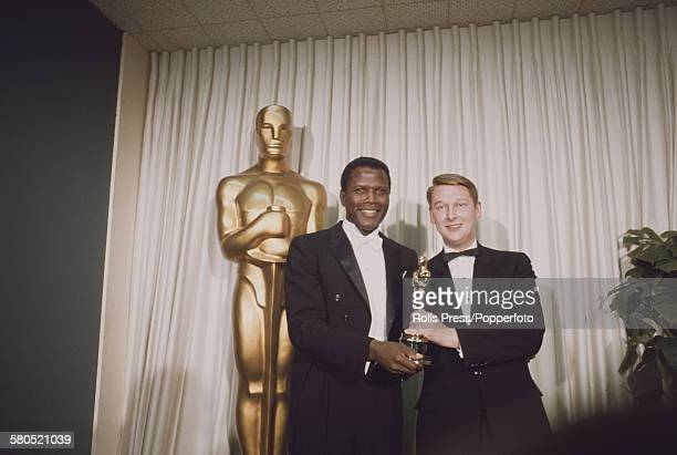 American actor Sidney Poitier left presents the Academy Award or Oscar for Best Director to Mike Nichols for his film The Graduate at the 40th...