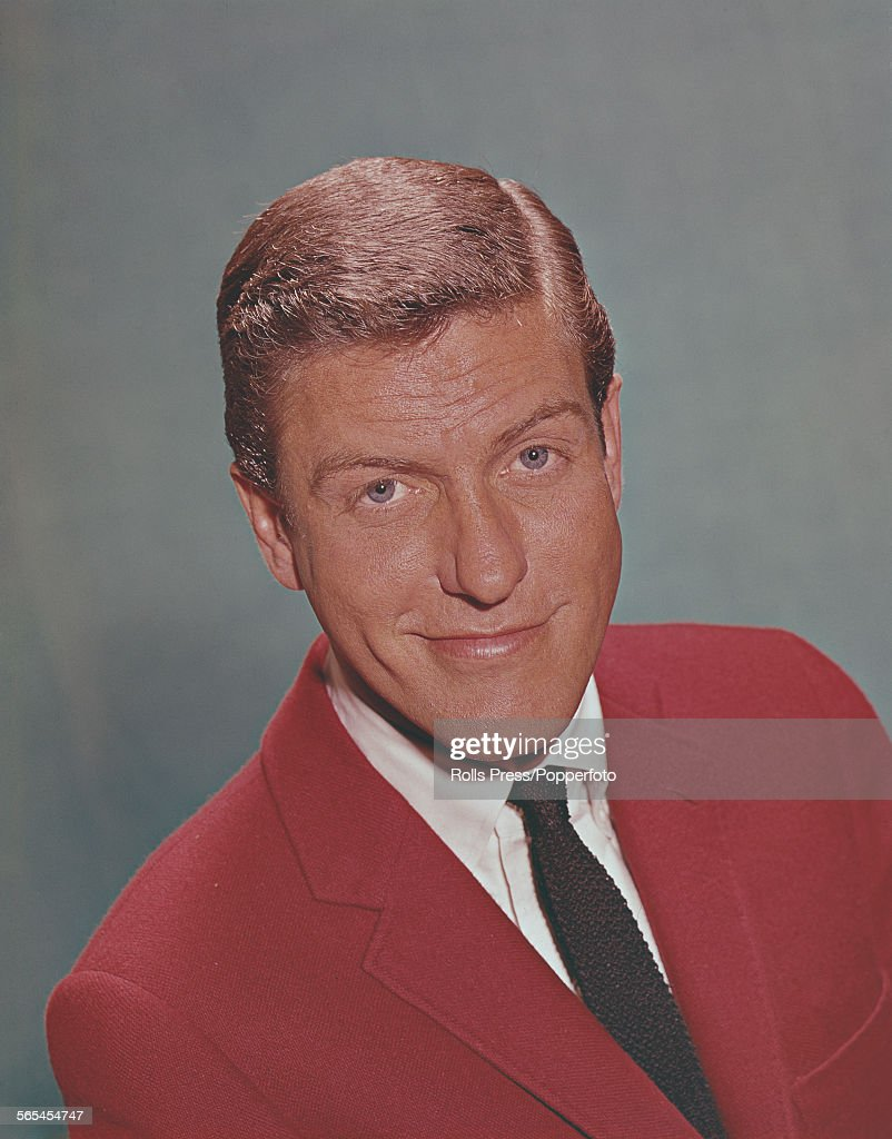 American actor singer and comedian Dick Van Dyke pictured wearing a red jacket white shirt and black tie circa 1967