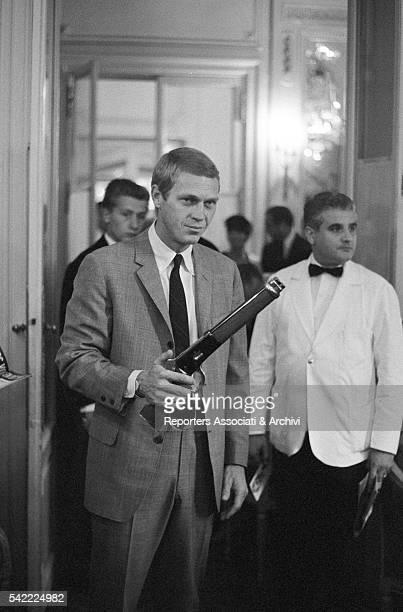 American actor Steve McQueen holding a fake gun during a party in Paris Paris September 1964