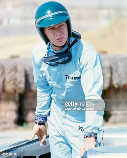 American actor Steve McQueen in Firestone racing driver suit near a Lola T70 SL70/14 car at Riverside Raceway in Riverside California circa 1966