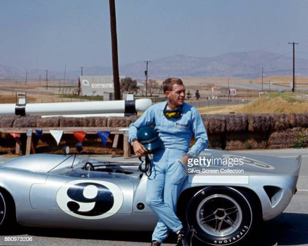 American actor Steve McQueen in Firestone racing suit leans against a Lola T70 SL70/14 car at Riverside Raceway Riverside California July 1966