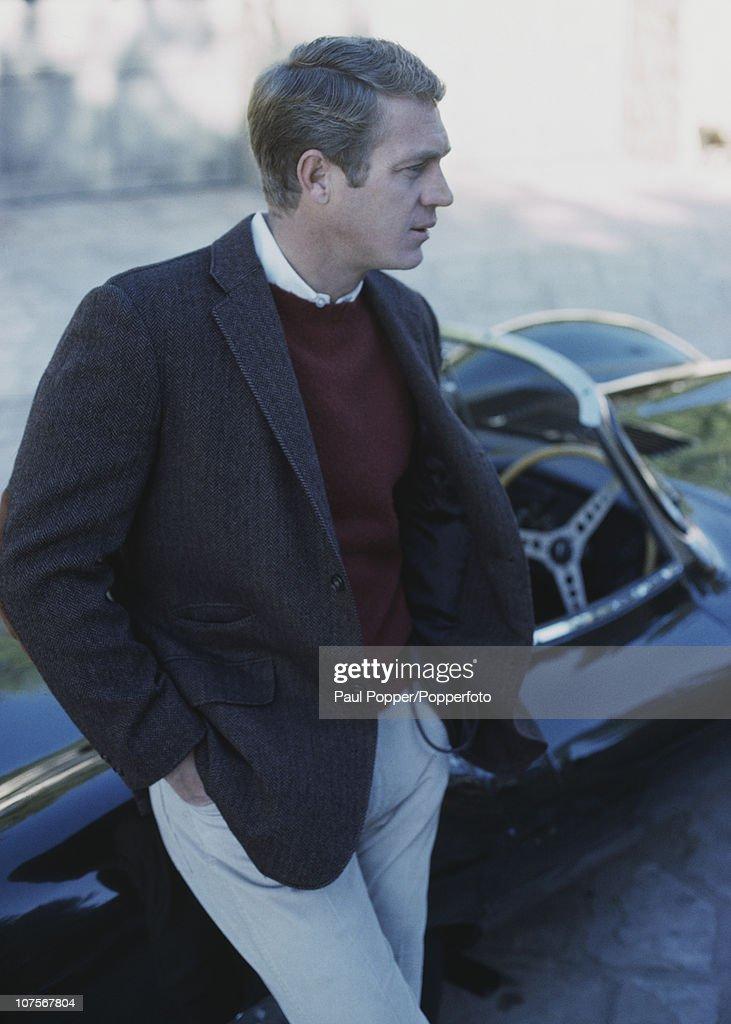 American actor Steve McQueen leaning on his Jaguar DType XKSS sports car 1965