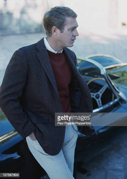 American actor Steve McQueen leaning on his Jaguar DType XKSS sports car 1965