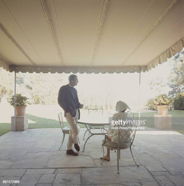 American actor Steve McQueen pictured standing on a verandah with his wife American actress Neile Adams sitting on a patio chair beside him circa 1971