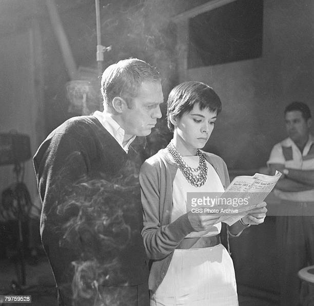 American actor Steve McQueen reads a newspaper over the shoulder of his wife Philippineborn actress Neile Adams during the filming of an episode of...