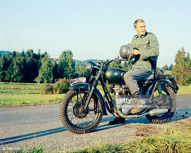 American actor Steve McQueen wearing a German military uniform sitting astride a Triumph Bonneville motorcycle in a publicity still issued for the...