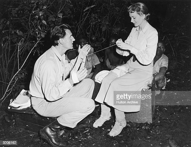 American actor Stewart Granger squats with yarn wrapped around his hands while Scottish actor Deborah Kerr knits on the set of directors Compton...