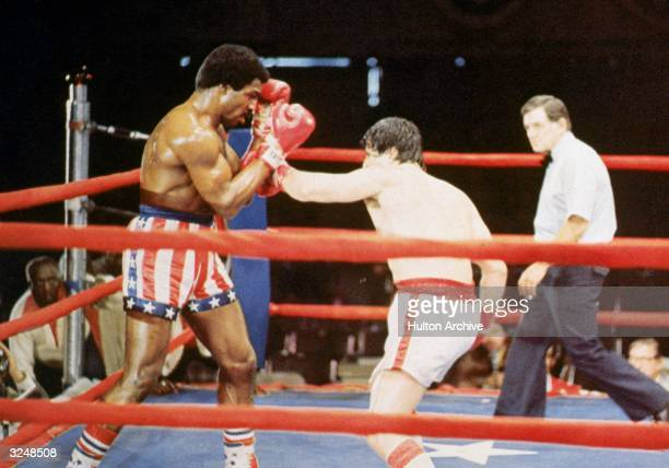 American actor Sylvester Stallone as Rocky Balboa punches American actor Carl Weathers as Apollo Creed during a boxing match in a still from the film...