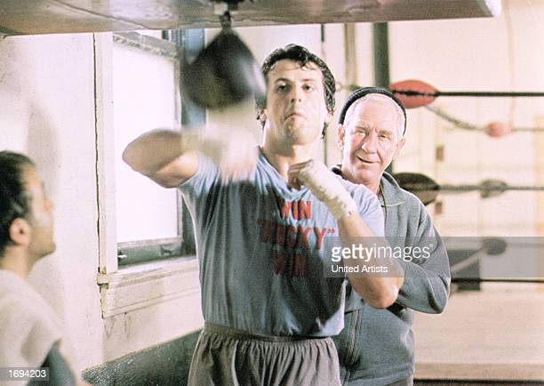 American actor Sylvester Stallone strikes at a punching bag in a boxing ring while his coach Burgess Meredith watches during training at a gymnasium...