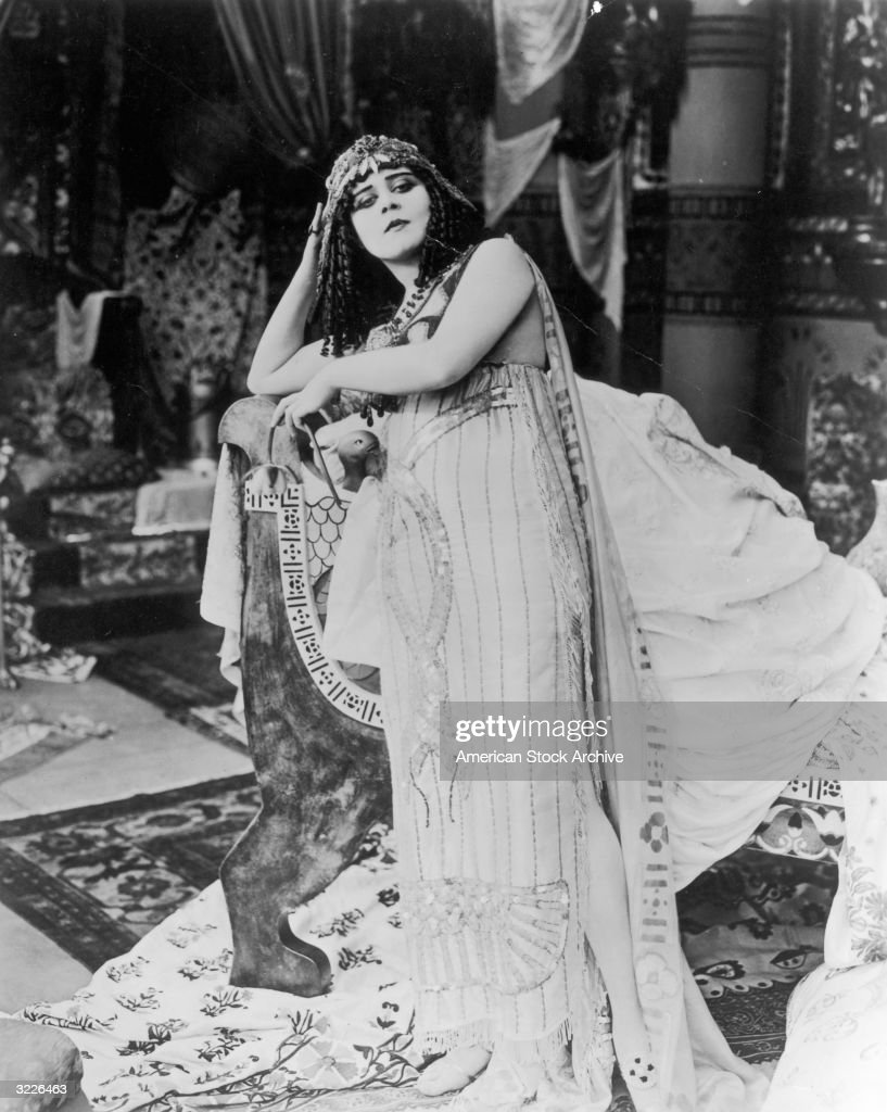 American actor Theda Bara, wearing a costume with entwined sequined snakes and a headdress, leans on a sofa in a still from director J Gordon Edwards' film '<a gi-track='captionPersonalityLinkClicked' href=/galleries/search?phrase=Cleopatra&family=editorial&specificpeople=105315 ng-click='$event.stopPropagation()'>Cleopatra</a>'.