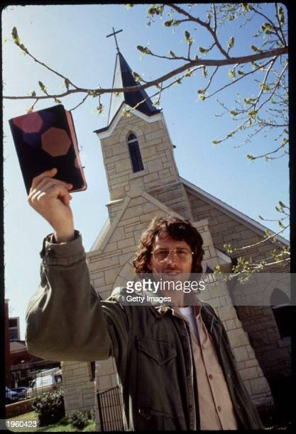 American actor Tim Daly holds up a Bible as he stands in front of a church on the set of the TV movie 'In the line of fire Ambush in Waco' Tulsa...
