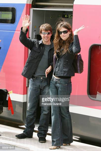 American actor Tom Cruise and his fiancee Katie Holmes wave to fans as they prepare to leave a Paris railway station for Marseille for the French...