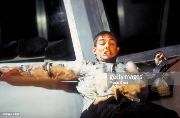 American actor Tom Cruise as Ethan Hunt filming a scene for the movie 'Mission Impossible' in a studio 1995 In this scene he clings to a replica of a...
