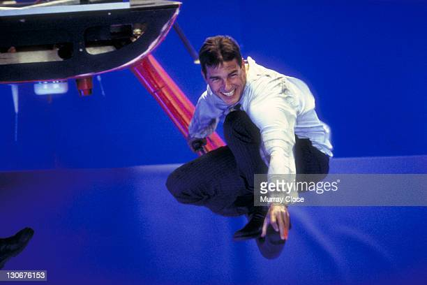 American actor Tom Cruise perches on a helicopter skid against a bluescreen whilst filming a scene for the movie 'Mission Impossible' at Pinewood...