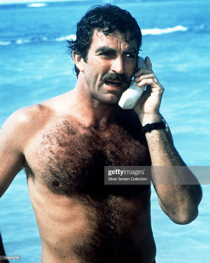American actor <a gi-track='captionPersonalityLinkClicked' href=/galleries/search?phrase=Tom+Selleck&family=editorial&specificpeople=208627 ng-click='$event.stopPropagation()'>Tom Selleck</a> as Thomas Magnum, making a mobile phone call from the beach, in the American TV series 'Magnum PI', circa 1985.