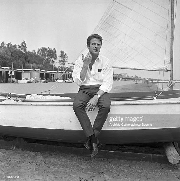 American actor Warren Beatty portrayed while sitting on a sail boat side on the Lido beach in front of the Excelsior Hotel Lido Venice 1956