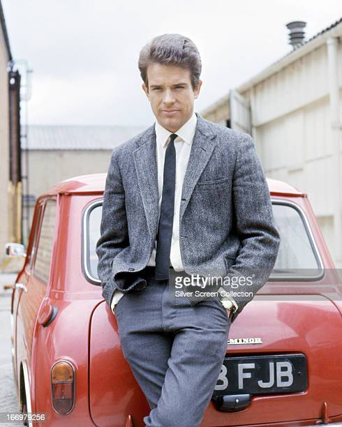 American actor Warren Beatty posing by a red Mini car in a promotional portrait for 'Kaleidoscope' directed by Jack Smight 1966
