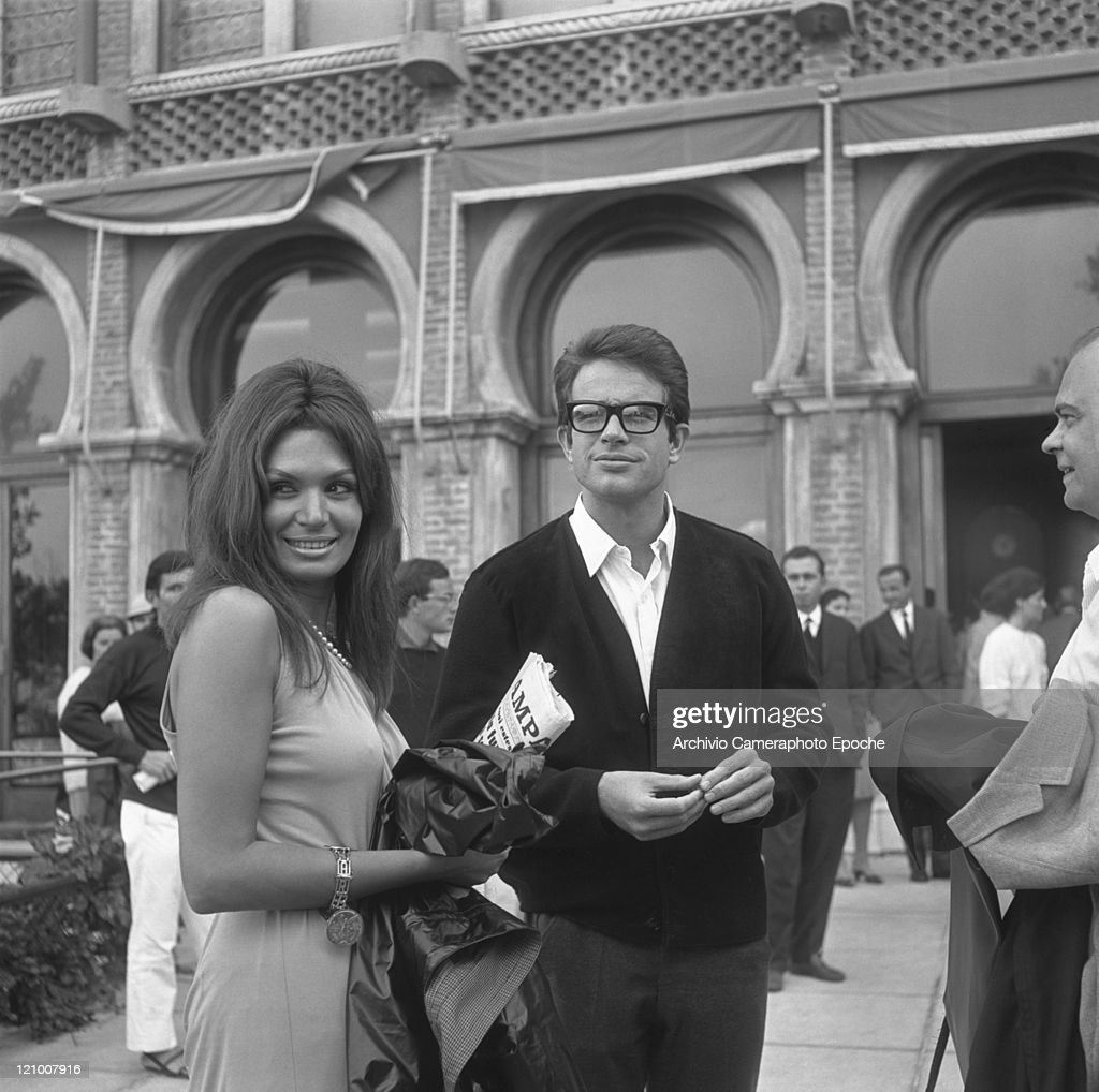 American actor Warren Beatty wearing a cardigan and glasses portrayed outside the Excelsior Hotel while standing next to a woman holding a newspaper...