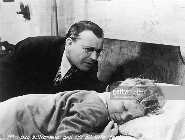 American actor Willard Robertson comforts American child actor Jackie Cooper who lies in bed in a still from the film 'Skippy' directed by Norman...