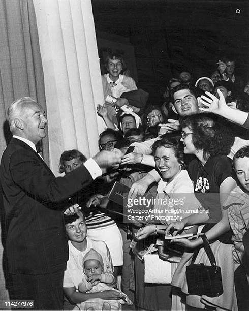 American actor William Boyd star of the 'Hopalong Cassidy' films and television series smiles as he signs autographs for fans 1950s Photo by Weegee...