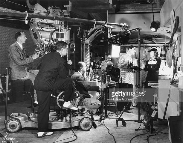 American actor William Powell plays an accordion for actor Myrna Loy while director Richard Thorpe sits on the set of his film 'Double Wedding' An...