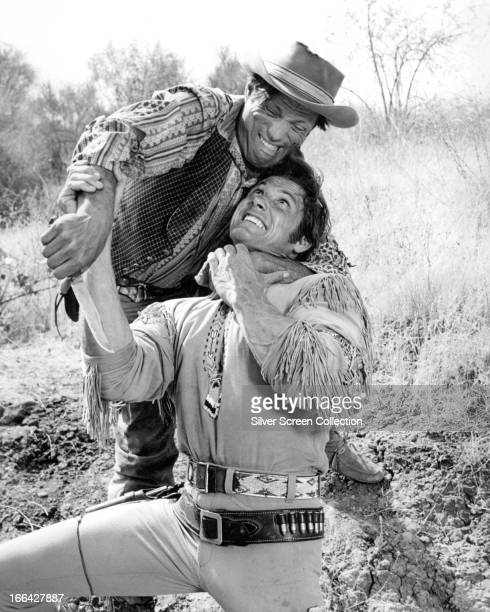 American actor William Smith struggles with a knifewielding assailant in a scene from a western circa 1965
