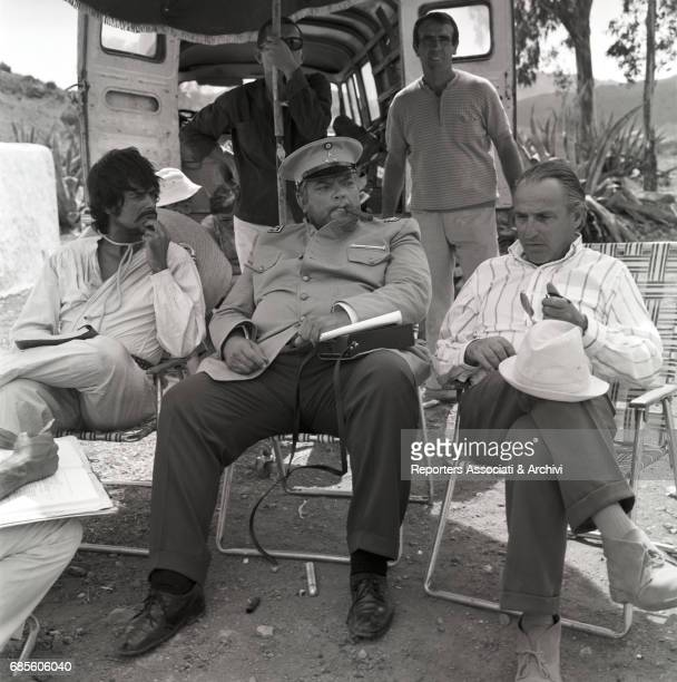 American actor writer and dramatist Orson Welles sitting and reading the script in colonel Cascorro costume sitting during a break with Cubanborn...