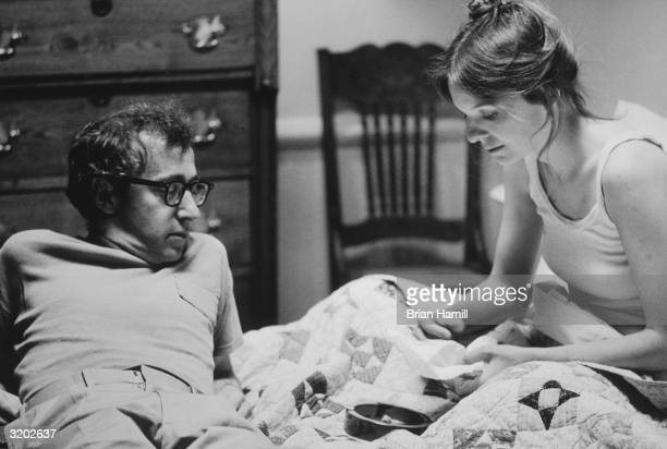 American actor writer and film director Woody Allen lays in bed leaning on his elbows by the feet of American actor Diane Keaton in a scene from...