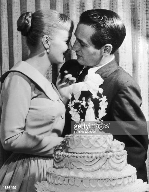 American actors and newlyweds Paul Newman and Joanne Woodward kiss behind a wedding cake during their wedding reception at the El Rancho hotelcasino...