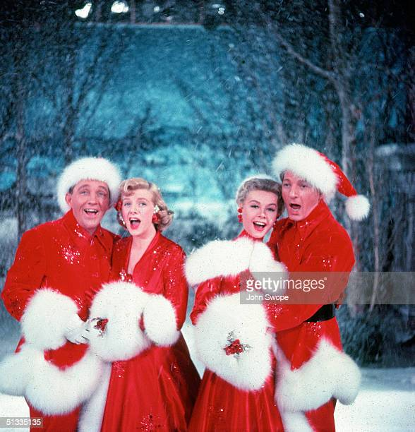 American actors Bing Crosby Rosemary Clooney VeraEllen and Danny Kaye sing together while dressed in furtrimmed red outfits and standing in front of...