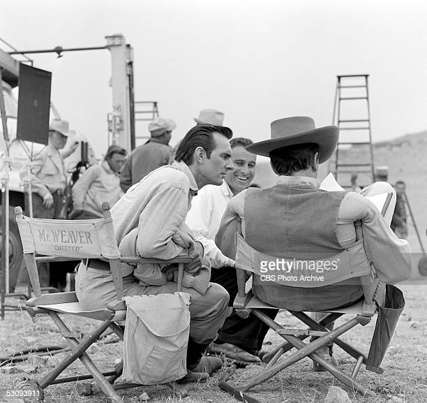 American actors Dennis Weaver and James Arness sit in their personalized director's chairs and look over a script on the set of the TV western...