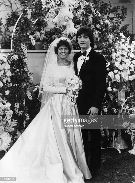 American actors Erin Moran wearing a wedding dress and Scott Baio wearing a tuxedo pose at an altar in a promotional portrait from the TV program...