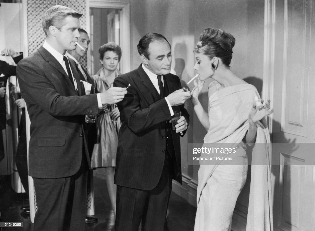 1961 American actors George Peppard and Martin Balsam compete to light Belgianborn actor Audrey Hepburn's cigarette at a formal party in a still from...