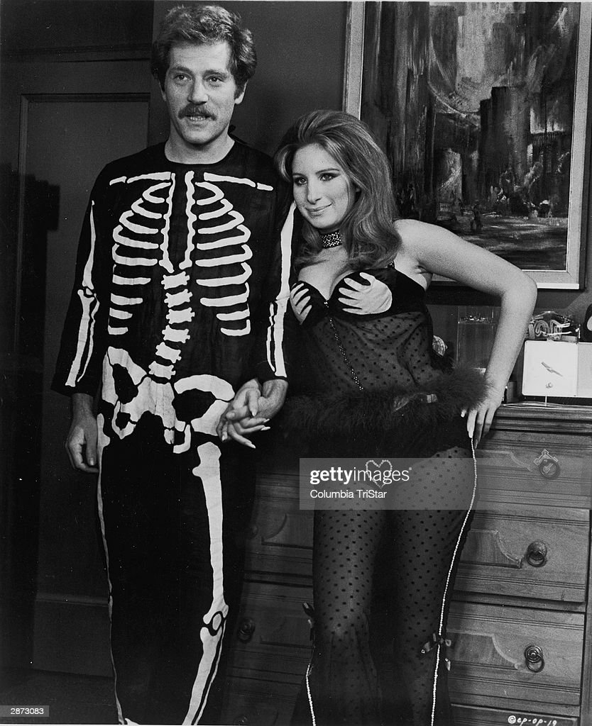 American actors George Segal and Barbra Streisand hold hands, wearing Halloween costumes, in a still from the film, 'The Owl And The Pussycat,' directed by Herbert Ross, 1970.