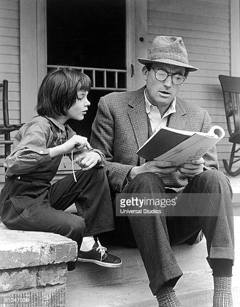 1962 American actors Gregory Peck and Mary Badham review the script for the film 'To Kill a Mockingbird' directed by Robert Mulligan on the set of...