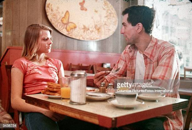 American actors Jodie Foster and Robert De Niro sit together at a diner in a still from the film 'Taxi Driver' directed by Martin Scorsese