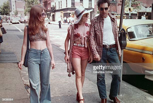 American actors Jodie Foster center and Robert De Niro walk past a parked taxi on a New York City street in a still from the film 'Taxi Driver'...