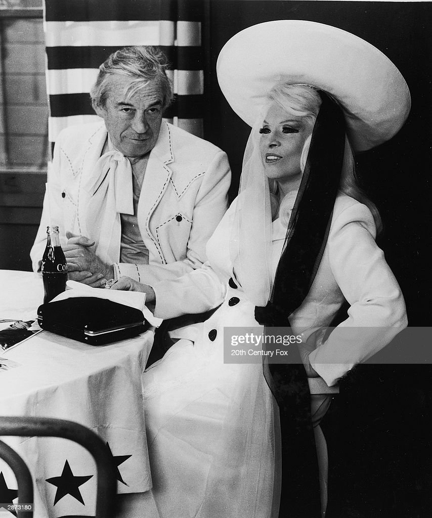 American actors John Huston and Mae West sit at a resturant table in a still from the film, 'Myra Breckinridge,' directed by Michael Sarne, 1970.