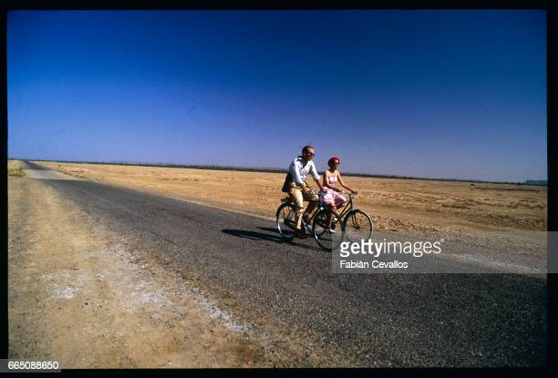 American actors John Malkovitch and Debra Winger ride bicyles on a road in the Moroccan desert during the shooting of the movie Un The au Sahara or...
