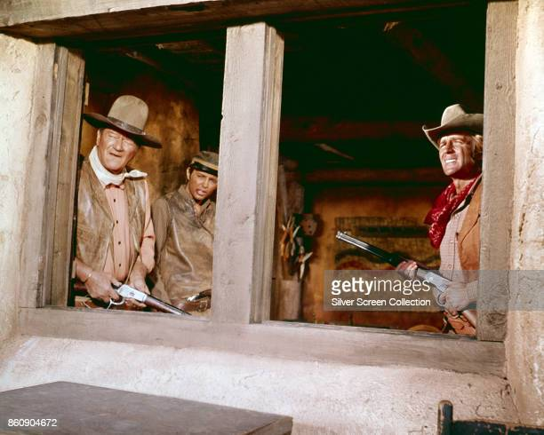 American actors John Wayne and Christopher Mitchum both with rifles as they look out of a window in a scene from 'Rio Lobo' 1970 The actor in the...
