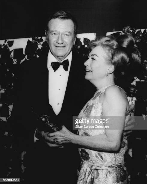 American actors John Wayne and Joan Crawford hold a trophy at 27th Annual Golden Globe Awards ceremony at the Cocoanut Grove Los Angeles California...