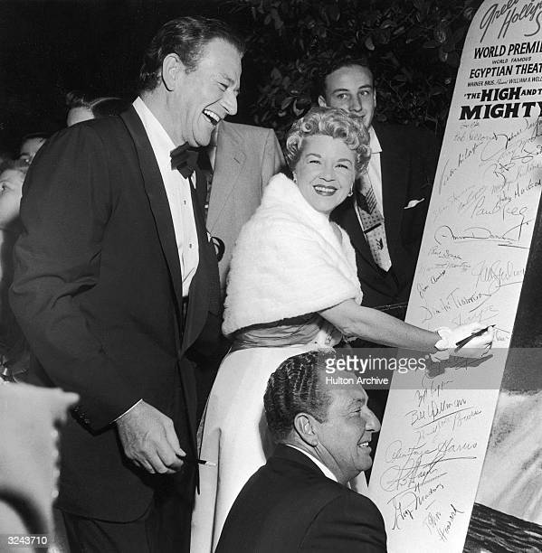 American actors John Wayne Claire Trevor with American actor and singer Phil Harris signing a tablet at the premiere of director William A Wellman's...