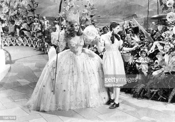 American actors Judy Garland and Billie Burke link hands surrounded by Munchkins in a still from the film 'The Wizard of Oz' directed by Victor...