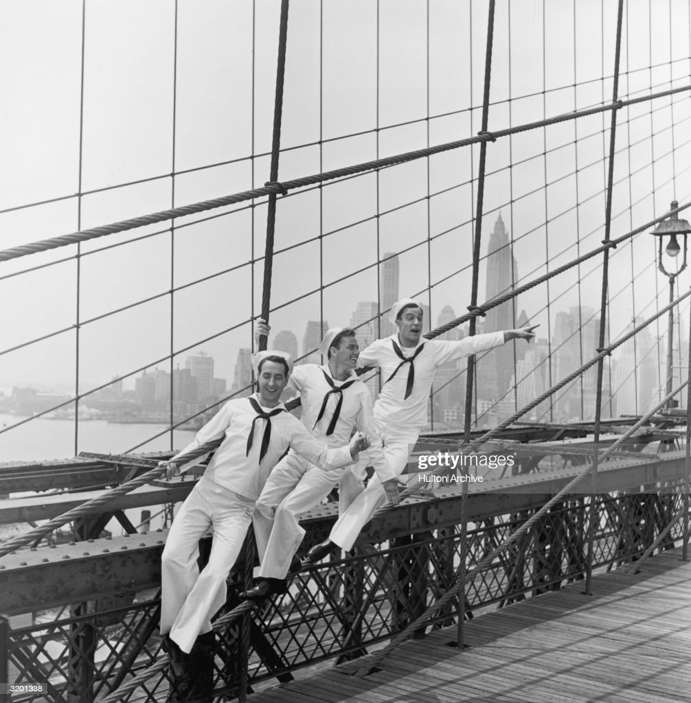 American actors Jules Munshin, Frank Sinatra and Gene Kelly standing on the Brooklyn Bridge in sailor's uniforms, in a still from Stanley Donen and Gene Kelly's film 'On the Town', New York City. With a view of the Manhattan skyline in the background. Music by Leonard Bernstein.