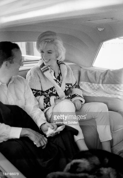 American actors Marilyn Monroe and Wally Cox share a laugh as they ride together after leaving the studio following a day's filming on the set of...