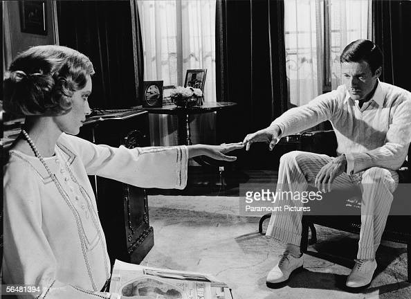 American actors Mia Farrow as Daisy Buchanan and Robert Redford as Jay Gatsby reach for one another across a room in a scene from 'The Great Gatsby'...