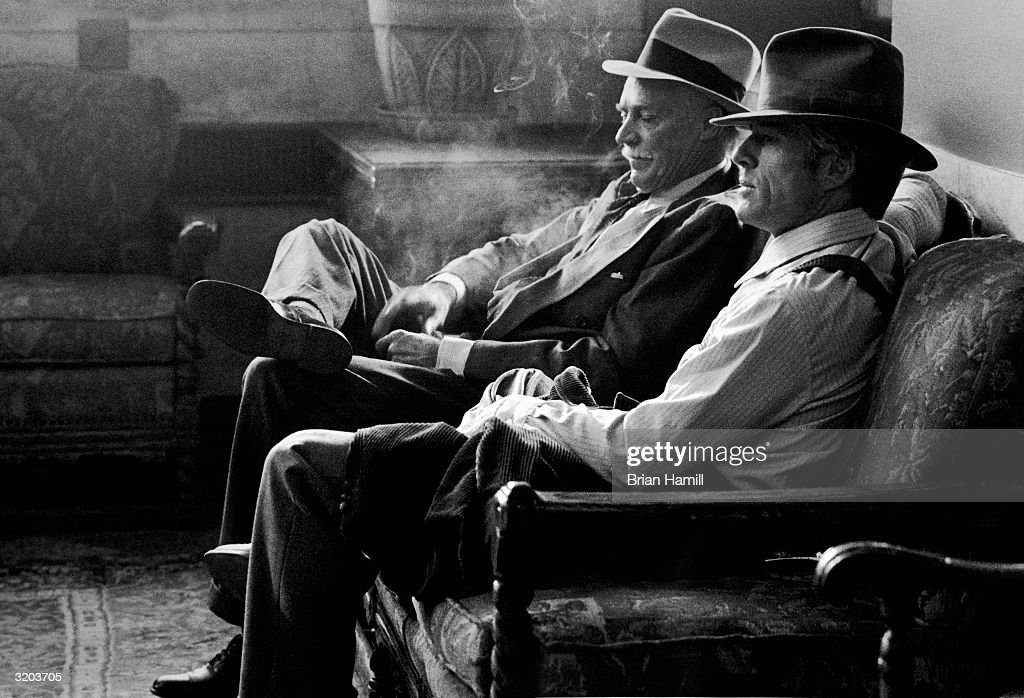 American actors Richard Farnsworth (L) and Robert Redford, sit together on a settee, in a still from director Barry Levinson's film, 'The Natural'. Both men wear hats and suits. RESTRICTED, PLEASE INQUIRE.